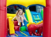Child jumping on playground trampoline. Kids jump. Child jumping on colorful playground trampoline. Kids jump in inflatable bounce castle on kindergarten Royalty Free Stock Photos