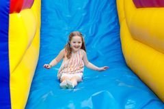 Child jumping on playground trampoline. Kids jump. Child jumping on colorful playground trampoline. Kids jump in inflatable bounce castle on kindergarten Royalty Free Stock Photography