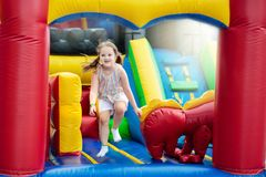 Child jumping on playground trampoline. Kids jump. Child jumping on colorful playground trampoline. Kids jump in inflatable bounce castle on kindergarten royalty free stock images