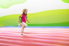 Child jumping on playground trampoline. Kids jump. Child jumping on colorful playground trampoline. Kids jump in inflatable bounce castle on kindergarten stock photos
