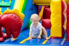 Child jumping on playground trampoline. Kids jump. Child jumping on colorful playground trampoline. Kids jump in inflatable bounce castle on kindergarten stock image