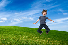 Child jumping on green field Royalty Free Stock Image