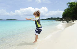 Child Jumping and having Fun on Tropical Beach near Ocean Royalty Free Stock Photo