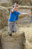 Child jumping in haystack royalty free stock image