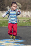 Child jumping hopscotch Royalty Free Stock Photography