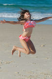 Child jumping for joy. Pretty little girl in swimsuit jumping for joy on a beach Royalty Free Stock Photography