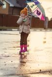 Child jumping in the muddy puddle. closeup of boots Stock Image
