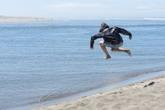 Child jumping off of sand dune Royalty Free Stock Photos