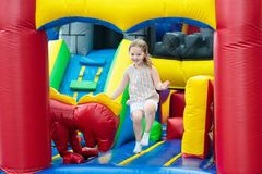 Child jumping on playground trampoline. Kids jump. Child jumping on colorful playground trampoline. Kids jump in inflatable bounce castle on kindergarten Royalty Free Stock Photo