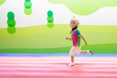 Child jumping on playground trampoline. Kids jump. Child jumping on colorful playground trampoline. Kids jump in inflatable bounce castle on kindergarten Royalty Free Stock Image