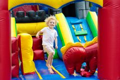 Child jumping on playground trampoline. Kids jump. Child jumping on colorful playground trampoline. Kids jump in inflatable bounce castle on kindergarten stock images