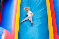 Child jumping on playground trampoline. Kids jump. Child jumping on colorful playground trampoline. Kids jump in inflatable bounce castle on kindergarten stock photo