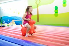Child jumping on playground trampoline. Kids jump. Child jumping on colorful playground trampoline. Kids jump in inflatable bounce castle on kindergarten Stock Photography