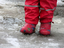 Child jumping for puddles on the roads thaw in the end of winter.  Royalty Free Stock Images
