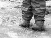 Child jumping for puddles on the roads thaw in the end of winter.  Royalty Free Stock Photos