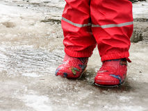 Child jumping for puddles on the roads thaw in the end of winter.  Royalty Free Stock Photography