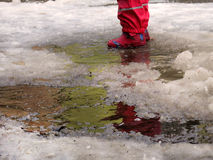 Child jumping for puddles on the roads thaw in the end of winter.  Stock Images