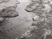 Child jumping for puddles on the roads thaw in the end of winter.  Stock Image