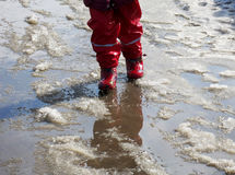 Child jumping for puddles on the roads thaw in the end of winter.  Royalty Free Stock Image