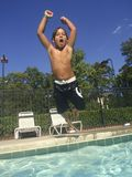 Child jumping in swimming pool. Happy young boy jumping into outdoor swimming pool Stock Photo