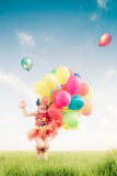 Child jumping with toy balloons in spring field Royalty Free Stock Photos