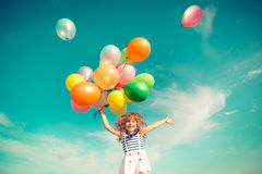 Child jumping with toy balloons in spring field. Happy child jumping with colorful toy balloons outdoors. Smiling kid having fun in green spring field against Stock Photo