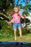 Child jumping trampoline. A cute little happy caucasian girl child showing her thumbs up and jumping up in the air on a trampoline on a sunny day outdoors Royalty Free Stock Photography