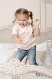 Child jumps on the bed. Portrait of smiling girl with braids Stock Photos