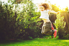 Child jumps on outdoors. Happy childhood concept. Stock Photos