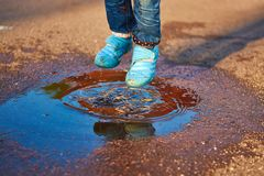 The child jumps in a puddle Royalty Free Stock Images