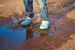 The child jumps in a puddle Stock Images
