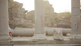 Child jumps on the stone ruins of the Roman era stock video footage