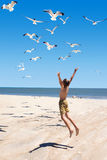 A child jumps towards flying seagulls Royalty Free Stock Images