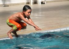 The child jumps in water. The boy dives into water of pool Royalty Free Stock Photo