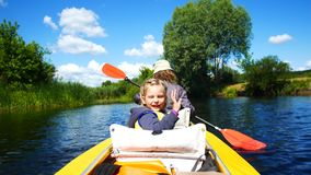 A child in a kayak on the river. Family outdoor activities.