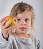 Child keeping up a apple. Girl keeping up a apple Stock Images