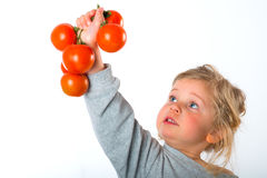Child keeping up tomato. Little girl keeping up tomato Royalty Free Stock Photos