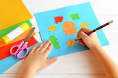 Child keeps a pencil in hand and draws. Scissors, glue stick, colorful paper, children applique. Cute paper sea animals. Kids skills. Crafts project idea Stock Images