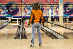 Child keeps track of thrown ball in bowling Royalty Free Stock Photos