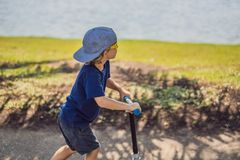 Child on kick scooter in park. Kids learn to skate roller board. Little boy skating on sunny summer day. Outdoor. Activity for children on safe residential royalty free stock image