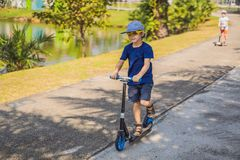 Child on kick scooter in park. Kids learn to skate roller board. Little boy skating on sunny summer day. Outdoor royalty free stock photos