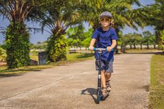 Child on kick scooter in park. Kids learn to skate roller board. Little boy skating on sunny summer day. Outdoor royalty free stock photography