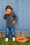 Child kid boy eating apple fruit full body portrait format autum. N fall healthy outdoors Stock Photo