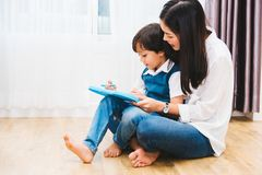 Child kid boy kindergarten and beautiful mother drawing together. At interior room home stock images