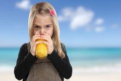 Child kid drinking orange juice beach summer sea healthy eating Stock Images