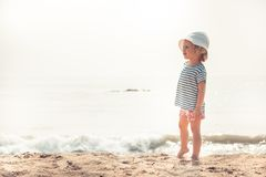Child kid girl on beach looking into the distance searching for something with bright sunlight concept happy childhood lifestyle. Child kid girl on beach looking royalty free stock photography