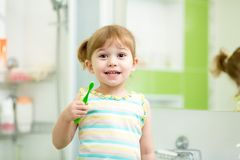 Child kid girl brushing teeth in bathroom Stock Image