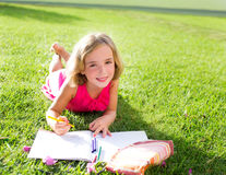 Child kid girl doing homework smiling happy on grass. Child kid girl doing homework smiling happy lying on grass garden with flowers Royalty Free Stock Image