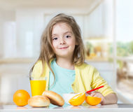 Child kid girl eating at table fruits indoors. Stock Image