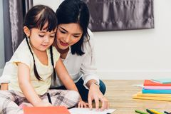Child kid girl kindergarten drawing teacher education mother with beautiful mother. At interior room home stock photos